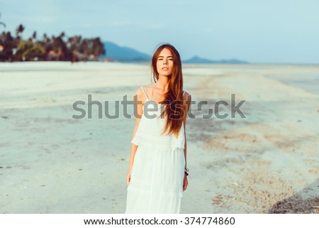 Outdoor fashion lifestyle summer vacation tropic portrait of pretty young beautiful sensual stunning woman blond hairs posing on the paradise beach - stock photo