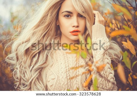 Outdoor fashion photo of young beautiful lady surrounded autumn leaves - stock photo