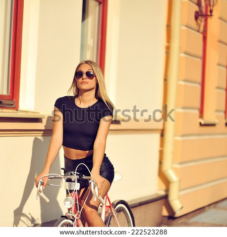 Outdoor fashion portrait of a beautiful blonde model with bike - stock photo