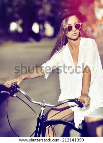 Outdoor fashion portrait of a beautiful woman on a bicycle - stock photo