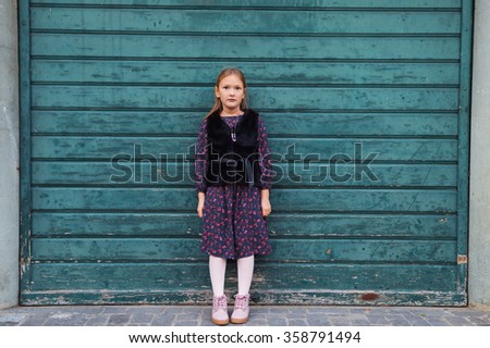 Outdoor fashion portrait of a cute little girl of 8 years old, wearing black dress and faux fur coat, standing next to green wooden wall - stock photo
