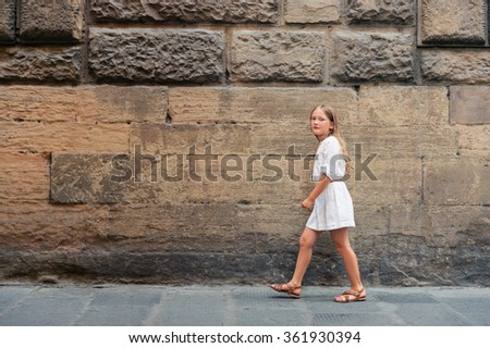 Outdoor fashion portrait of a pretty little girl, wearing white dress and summer sandals - stock photo