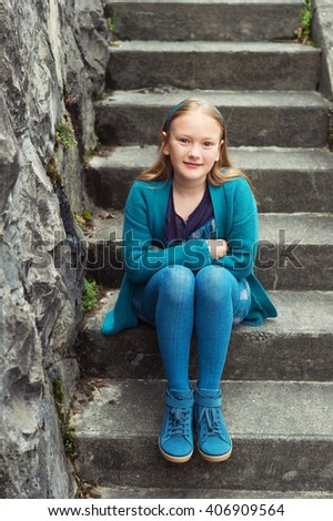Outdoor fashion portrait of adorable little girl of 8-9 years old, wearing blue clothes and shoes, sitting on stairs in a city - stock photo