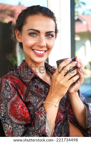 Outdoor fashion portrait of beautiful woman with big amazing smile and natural make up, holding cup of tea in her hands. Morning romantic atmosphere. - stock photo