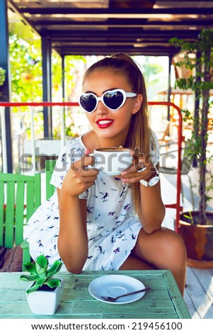Outdoor fashion portrait of beautiful young girl drinking tea alone on cute retro terrace and whiting for her friends, wearing vintage white pin up styled dress and heart sunglasses. - stock photo