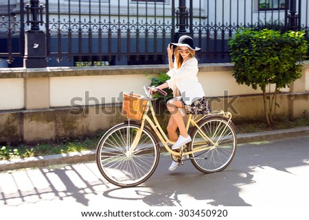 Outdoor fashion portrait of elegant lady riding her hipster retro bike in vintage stylish maxi skirt warm cardigan and straw hat.enjoy mica fall autumn day,posing at the street with birch trees.casual - stock photo