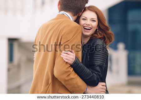 Outdoor fashion portrait of happy smiling couple in love having fun together end enjoy their love and romantic date. Close up portrait of loving couple  - stock photo