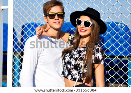 Outdoor fashion portrait of hipster couple in love hugs at sport ground, trendy black and white clothes, vintage sunglasses, posing at romantic date, sunny day, bright colors, love, relations. - stock photo