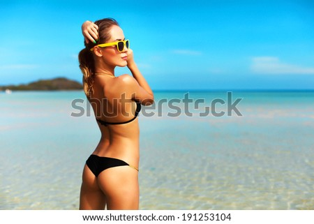Outdoor fashion portrait of pretty sexy sensual woman in black bikini posing outdoor in summer on tropic island on the beach near blue sea and sky and having fun on vacation - stock photo