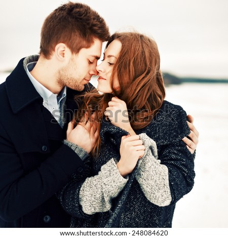 Outdoor fashion portrait of pretty young couple in love in winter cold weather feeling together happy