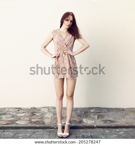 Outdoor fashion portrait of pretty young sensual woman posing on the street in summer in short vintage dress