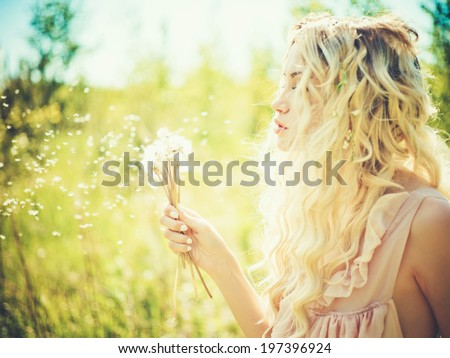 Outdoor fashion portrait of romantic blonde with dandelions - stock photo