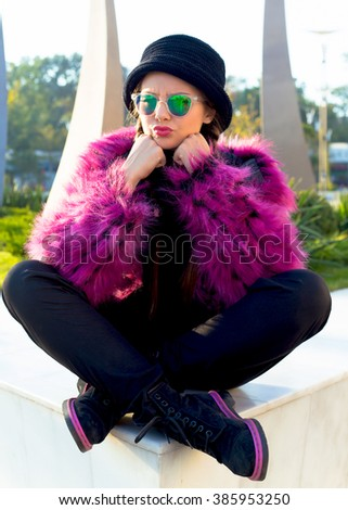 Outdoor fashion portrait of stunning pretty hipster girl,vintage hat,trendy faux fur coat, violet background. Sitting on the floor,crazy cheeky angry surprised emotions.Dissapoitment and stress.