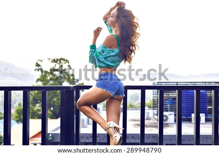 Outdoor fashion portrait of stunning  sensual woman with perfect tanned fit body posing on balcony, windy weather, stylish outfit, toned colors. - stock photo