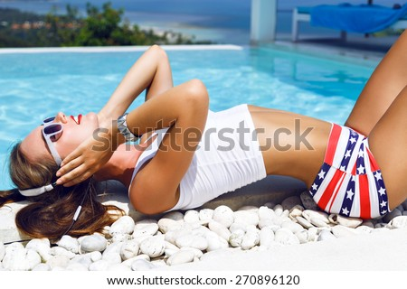 Outdoor fashion portrait of stunning woman with perfect body, relaxing near pool with amazing view on ocean and tropical island, enjoy the music on earphones, wearing sexy summer outfit. - stock photo