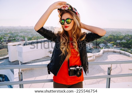 Outdoor fashion portrait of stylish photographer girl holding vintage retro camera, wearing bright swag hat, trendy sunglasses and leather jacket, amazing view of city from the roof. - stock photo