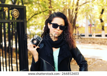 Outdoor fashion portrait of stylish photographer girl holding vintage retro camera, wearing trendy sunglasses and leather jacket. Lifestyle portrait bright toned colors.