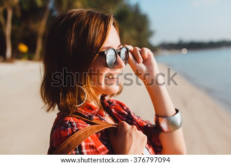 Outdoor fashion portrait of stylish photographer girl, trendy sunglasses amazing view of beach, hipster style, close up fashion,fresh face smiling on the beach of tropic island having fun on vacation