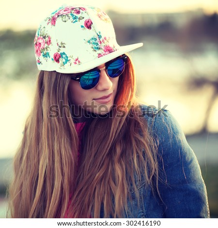 Outdoor fashion portrait of stylish swag girl, wearing swag cap, trendy sunglasses and denim jacket, amazing view of the beach at sunset. Lifestyle picture toned with a vintage instagram filter effect - stock photo