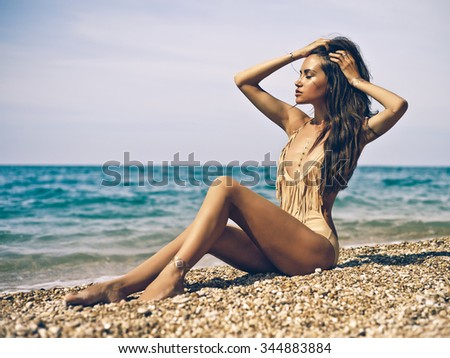 Outdoor fashion portrait of tanned lady in sexual swimsuit posing at beach - stock photo