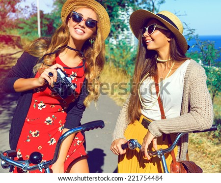 Outdoor fashion portrait of two hipster girls smiling laughing and have perfect free day together, walking with retro bicycles, taking pictures on retro camera, wearing stylish vintage outfits . - stock photo