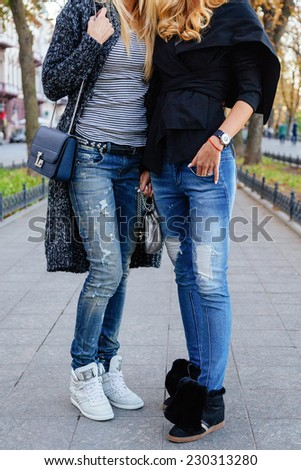 Outdoor fashion portrait of two stylish girls wearing trendy fall autumn outfits, cozy jackets denim and sneakers. Street style look.