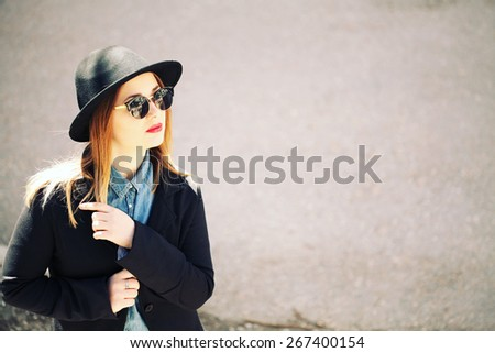 Outdoor fashion portrait of young beautiful blonde woman in denim shirt, black jacket and sunglasses. Beautiful cool girl in hat. Lifestyle - stock photo