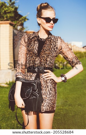 Outdoor fashion portrait of young beautiful stylish woman wearing mini printed dress casual black leather bag with spikes, and retro cat eye sunglasses. - stock photo