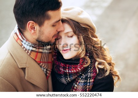 Outdoor fashion portrait of young couple in love in cold weather in city streets. A romantic date, st. Valentine