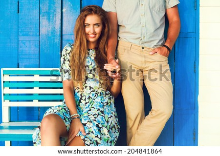 Outdoor fashion portrait of young couple in love posing at blue chubby chick beach cafe, holding hands end enjoy time together. - stock photo