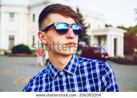 Outdoor fashion portrait of young handsome hipster man with stylish haircut posing at city in plaid shirt and mirrored sunglasses. - stock photo