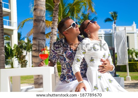 Outdoor fashion portrait of young sensual couple in vacation. Attractive elegant young couple drinking a cocktail. Luxury vacation - stock photo
