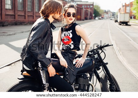 outdoor fashion portrait of young sensual couple sitting on vintage motorcycle