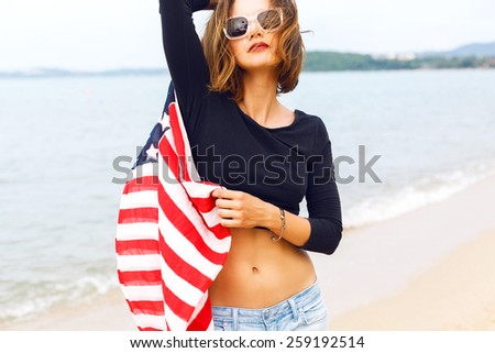Outdoor fashion portrait of young sensual woman, wearing retro old school denim jeans crop top and sunglasses,  holding american flag, posing near sea at rainy day, romantic atmosphere, vintage style. - stock photo