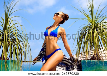 Outdoor fashion portrait of young sexy model woman with perfect slim fit tanned body, enjoy her summer vacation on luxury villa, amazing view on  island ocean, wearing bikini and sunglasses. - stock photo