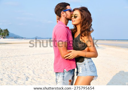Outdoor fashion portrait of young stylish couple in love hugs and kisses on the beach at nice sunny summer day, wearing casual outfits and sunglasses.