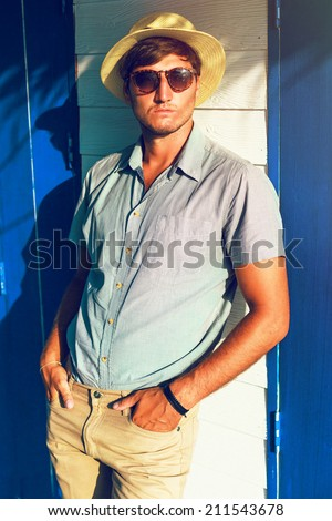 Outdoor fashion portrait of young stylish guy posing at sunny day beach cafe with wooden walls in stylish classic look with hat and sunglasses. - stock photo