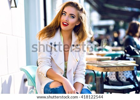 Outdoor fashion portrait of young stylish stunning woman, wearing hipster jeans and elegant coat, glamour bright make up, posing at city cafe terrace, traveling clone, sunny day. - stock photo