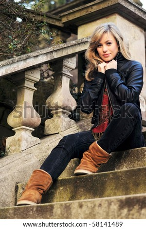Outdoor Fashion Portrait Of Young Woman SItting On Steps