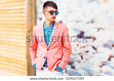 Outdoor fashion portrait portrait of young stylish hipster man, wearing trendy classic casual bright clothes and sunglasses, soft pastel colors. - stock photo