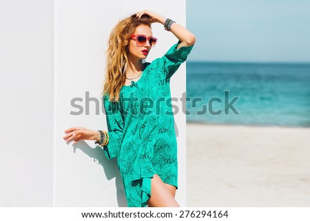 Outdoor fashion summer portrait of beautiful  slim tan woman with perfect bode in bright boho beach dress and cool  accessories , stylish sunglasses on the paradise tropical  breach. - stock photo