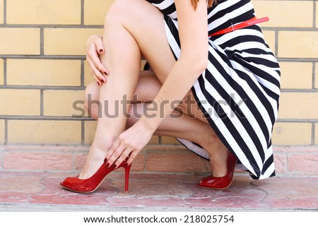 Outdoor fashionable girl near street wall legs in red high heel shoes and short striped dress outdoor shot - stock photo