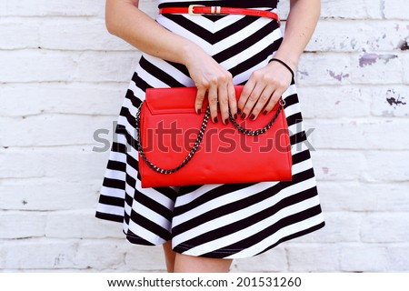 Outdoor Fashionable girl near white street wall .Marine and retro style. striped dress with red handbag clutch - stock photo