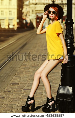Outdoor full body portrait of young beautiful fashionable lady posing on street. Model wearing stylish summer clothes. Girl looking at camera. Female fashion concept. City lifestyle. Sunny day