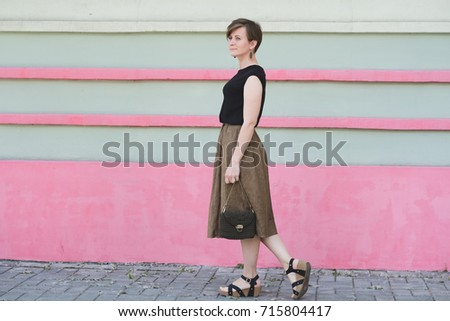 Outdoor full body portrait of young beautiful fashionable woman with small khaki bag