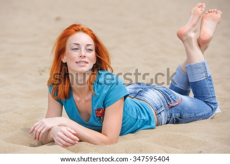Outdoor full-length portrait of a beautiful redhead woman lying relaxed on a sand - stock photo