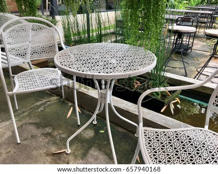 outdoor furniture white steel chairs and table in the zen garden landscape