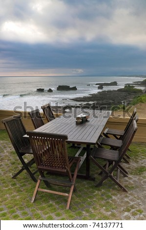 Outdoor furniture, with table, chairs and sea view - stock photo