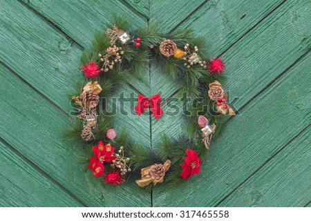 Outdoor hanging Christmas adorn wreath at an old green wooden door background - stock photo