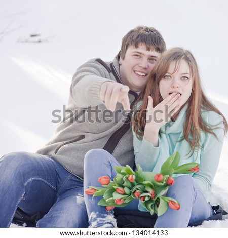 Outdoor happy couple in love with a bouquet of tulips, posing in cold weather and waiting for spring